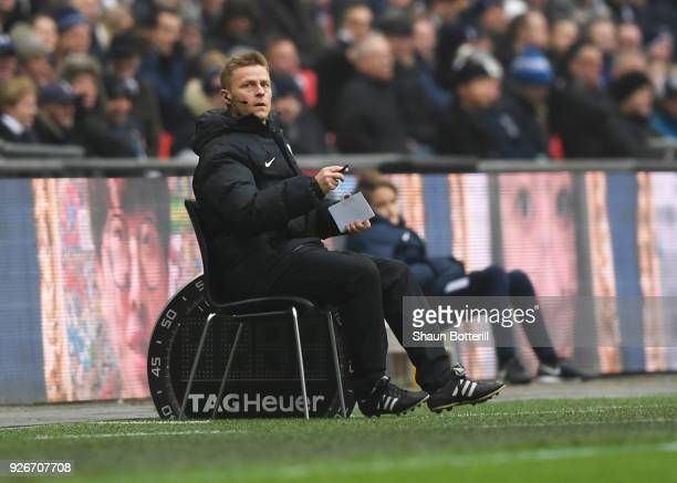 Injured referee Mike Jones sits on a chair pitchside as he operates as fourth official during the Premier League match between Tottenham Hotspur and...
