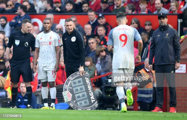 Injured Roberto Firmino of Liverpool is replaced by Daniel Sturridge of Liverpool during the Premier League match between Manchester United and...