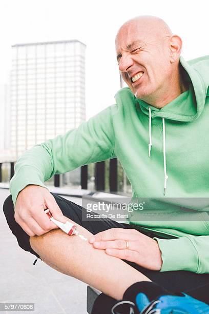 Blessé Runner appliquant des onguents sur sa jambe