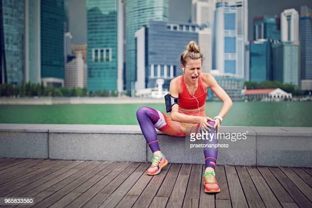 chica de la lesionados de la runner está sentado y sosteniendo su rodilla - herida rodilla fotografías e imágenes de stock