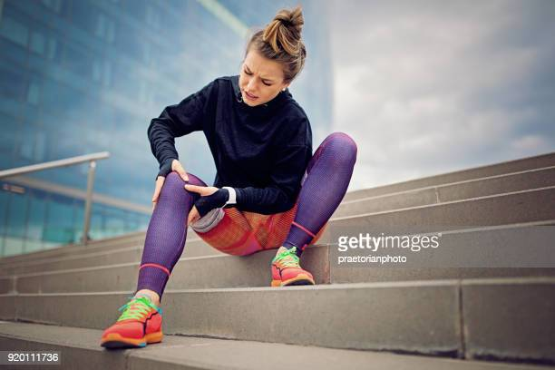 injured runner girl is sitting on the city stairs and holding her knee - down on one knee stock pictures, royalty-free photos & images