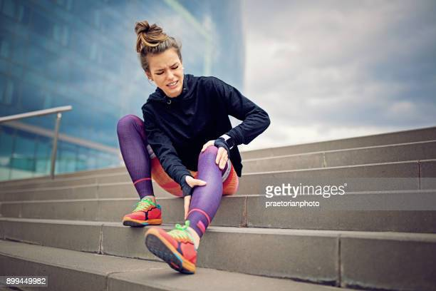 injured runner girl is sitting on the city stairs - personal injury stock photos and pictures