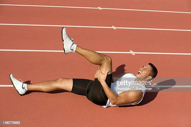 Injured runner lying on running track