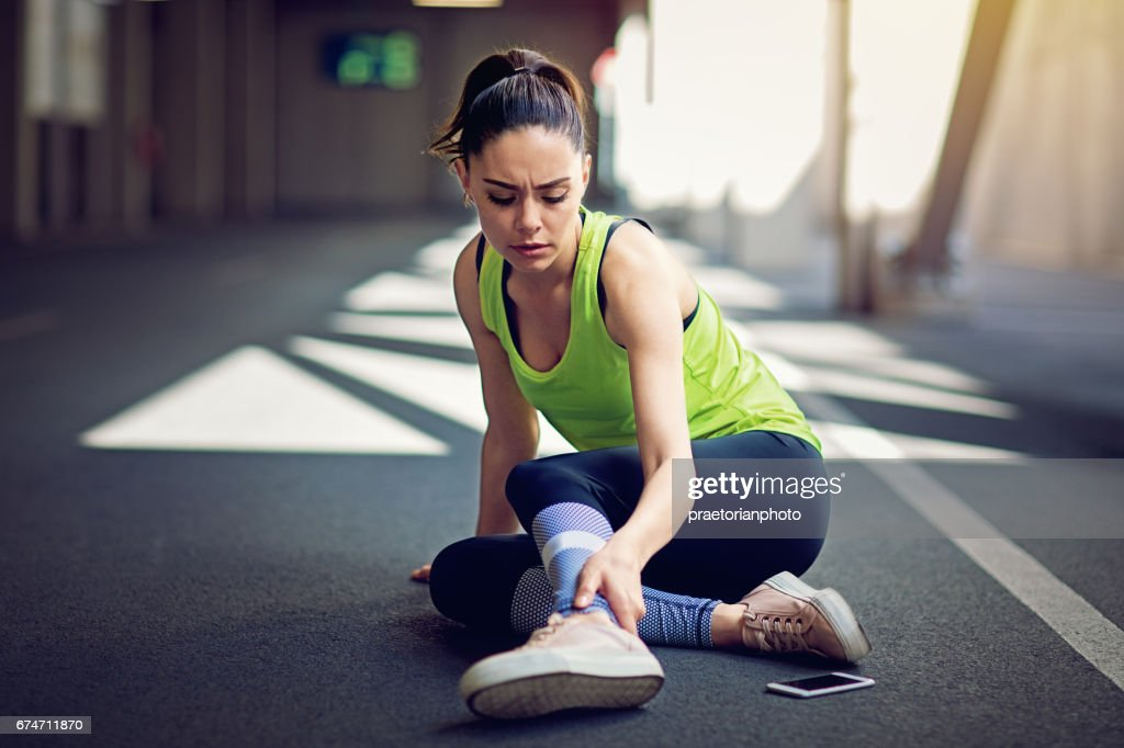 Injured runner sitting on the ground with broken mobile phone : Stock Photo