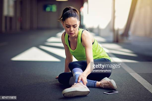 injured runner sitting on the ground with broken mobile phone - personal injury stock photos and pictures