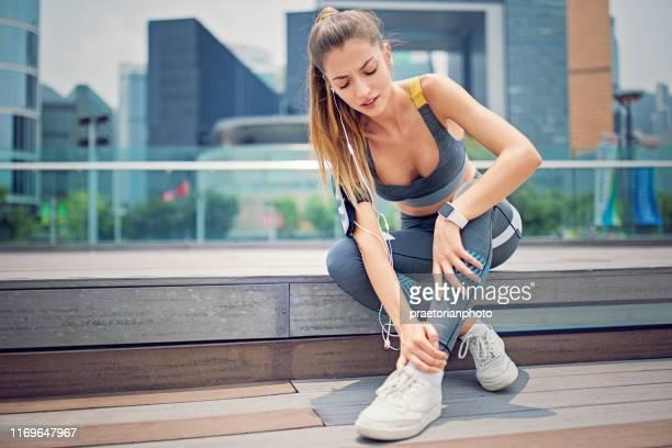 la runner donna ferita è seduta sulle scale della città - condizione foto e immagini stock