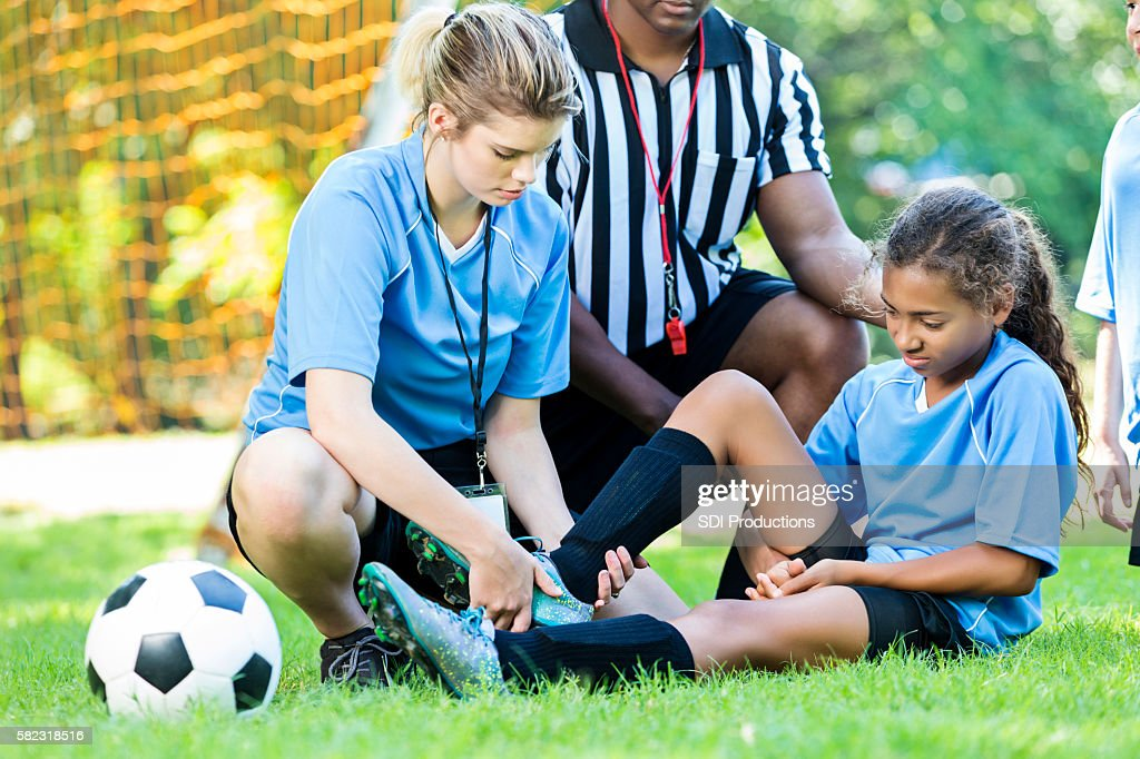 Injured soccer player getting her ankle checked by her coach : Stock Photo