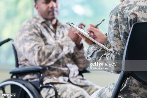 injured soldier talks with mental health professional - military doctor stock photos and pictures