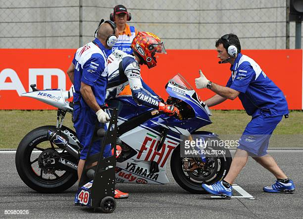 Injured Spanish MotoGP rider Jorge Lorenzo from the Yamaha Team is balanced by team members before the start of warm up lap at the China Grand Prix...