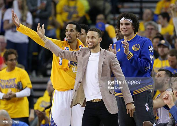 Injured Stephen Curry of the Golden State Warriors reacts on the bench with Shaun Livingston and Anderson Varejao during their game against the...
