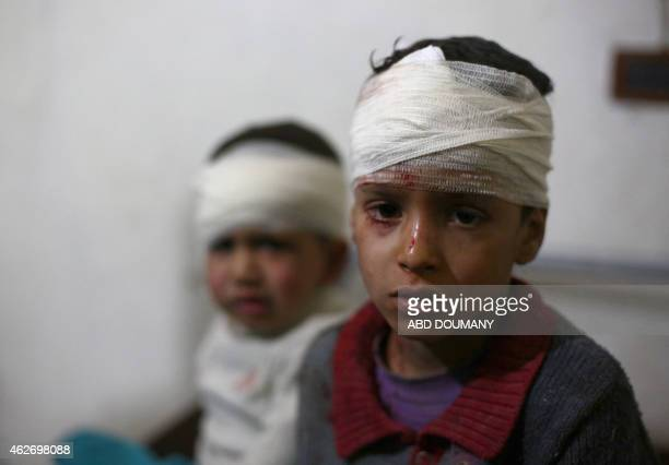Injured Syrian boys receive treatment at a makeshift hospital in the rebel held area of Douma, north east of the capital Damascus, following reported...