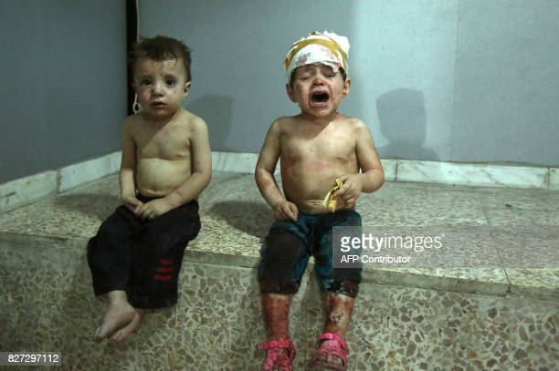 Injured Syrian children cry as they wait to receive treatment at a makeshift hospital in Jobar on August 5 following a reported government airstrike...