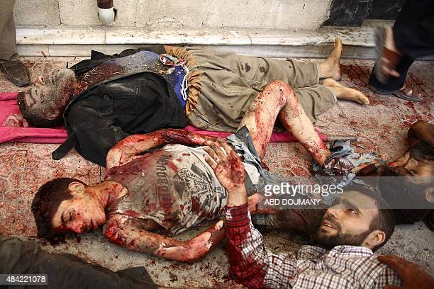 A injured Syrian man waits to receive treatment as he lies next to dead bodies at a makeshift hospital in the rebelheld area of Douma east of the...
