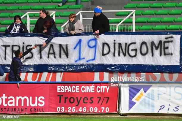 Injured Tristan Dingome of Troyes greets fans holding a banner supporting him before the Ligue 1 match between Troyes Estac and EA Guingamp at Stade...