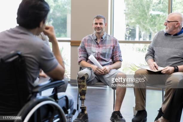 負傷した退役軍人が支援グループミーティング中に互いに話し合う - 四肢切断 ストックフォトと画像