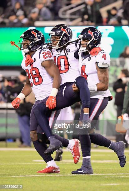 Injured wide receiver DeAndre Hopkins of the Houston Texans is carried off the field by teammates running back Alfred Blue and quarterback Deshaun...