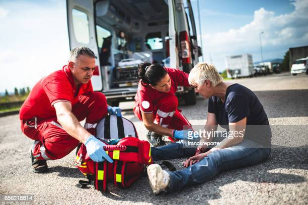 injured woman at the edge of the road - rescue worker stock pictures, royalty-free photos & images