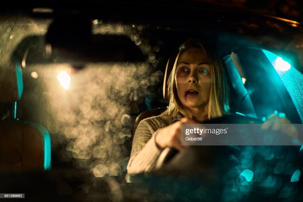Injured woman driving a car : Stock Photo