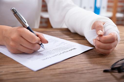 Injured Woman Filling Work Injury Claim Form 1125365656