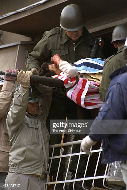 A injured woman is rescued by the members of the Japan Ground SelfDefense Force after the strong earthquake on January 18 1995 in Nishinomiya Hyogo...