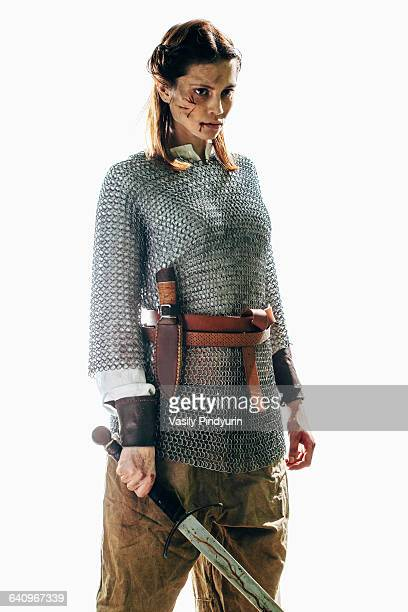 Injured woman wearing chain mail holding sword against white background