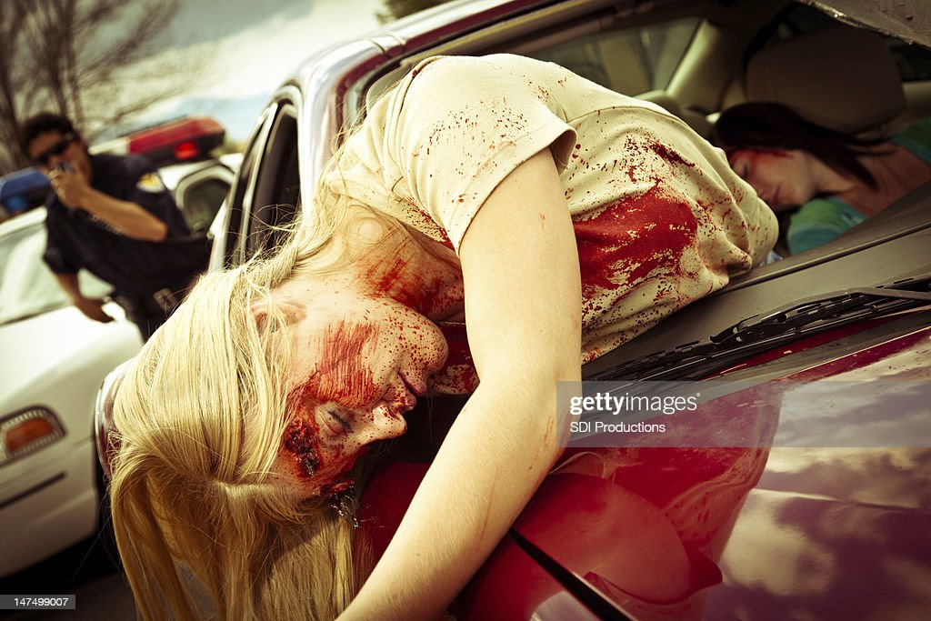 Injured Women in a Car after Accident with policeman responding : Stock Photo