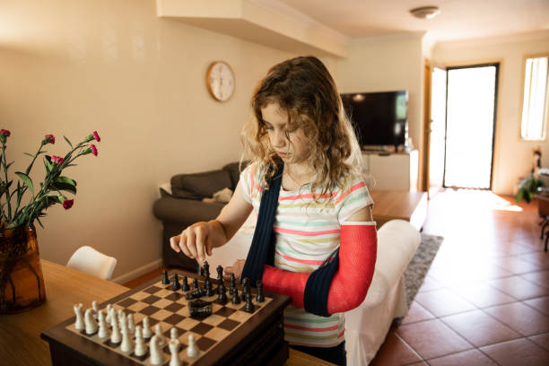 Injured young girl in cast playing chess at home