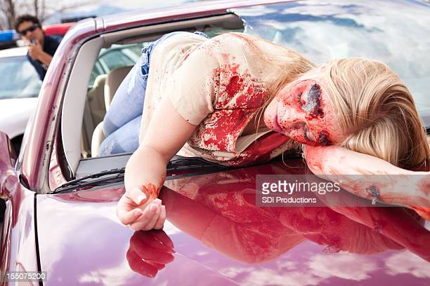 injured young woman on hood of car from an accident - dead female bodies stockfoto's en -beelden