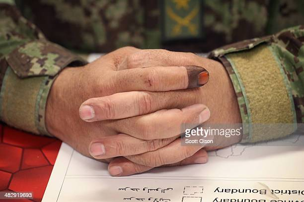 Ink stains the finger of a soldier with the Afghan National Army proof that he voted while he works in the tactical operations center at Camp Maiwand...