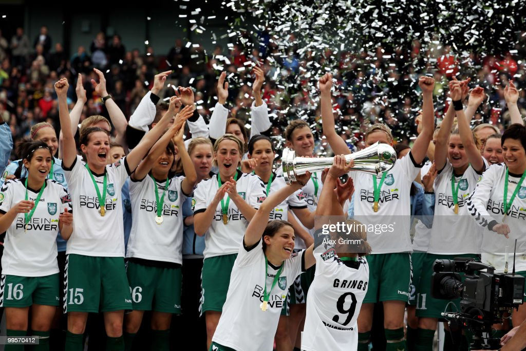 Inka Grings (front, R) and Annike Krahn (L) of Duisburg hold up the trophy after winning the DFB Women's Cup final match between FCR 2001 Duisburg and FF USV Jena at RheinEnergie stadium on May 15, 2010 in Cologne, Germany.