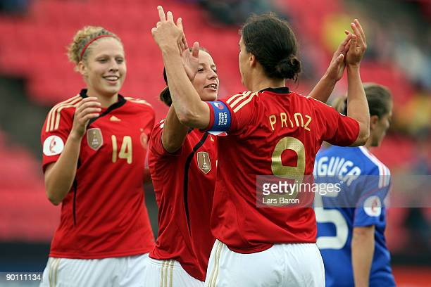 Inka Grings of Germany celebrates scoring the first goal with team mates Kim Kulig and Birgit Prinz during the UEFA Women's Euro 2009 group B...