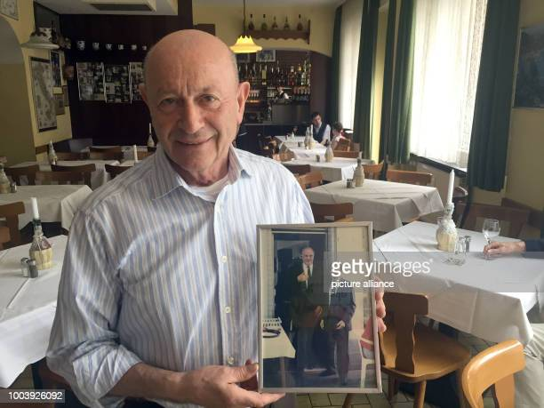 Inkeep Bruno Bellini holds a picture on which he can be seen with former chancellor Helmut Schmidt at the restaurant Da Bruno in Mainz Germany 17...