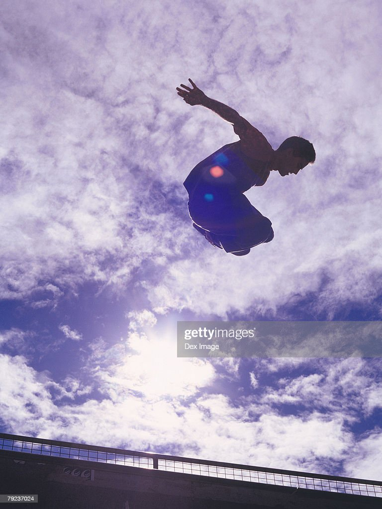 In-line skater performing stunt in mid-air : Stock Photo