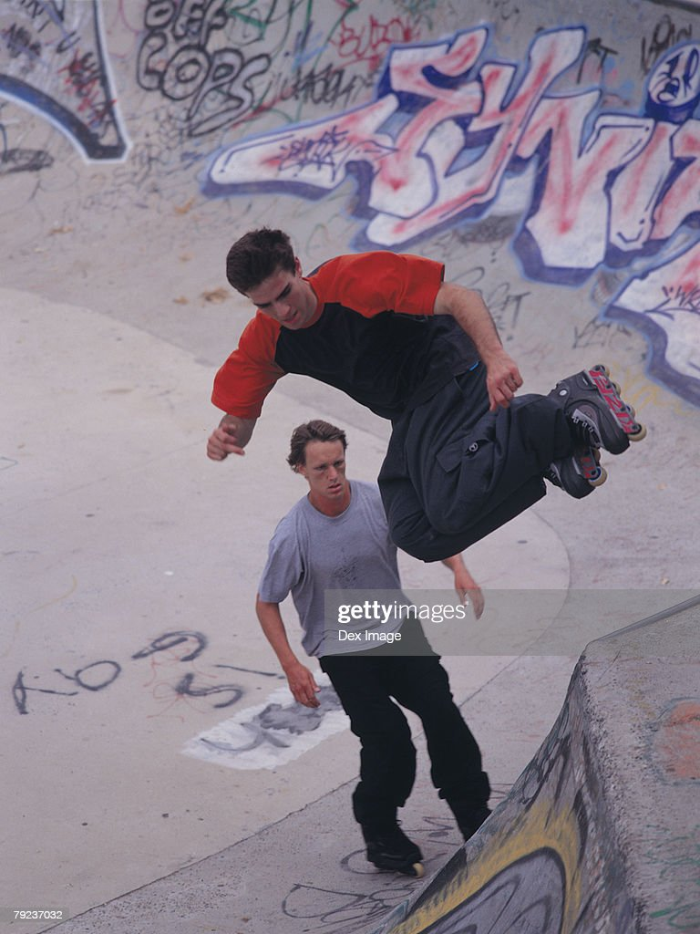 In-line skater performing stunt on ramp, mid-air : Stock Photo