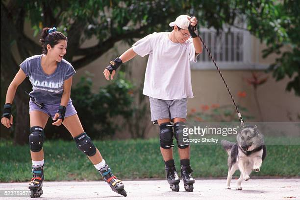 inline skating with their dog - dog pad foto e immagini stock