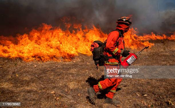 Inmate crews set backfires to heavy brush along Madera Rd as firefighters try to keep the Easy fire from crossing the road into Thousand Oaks...