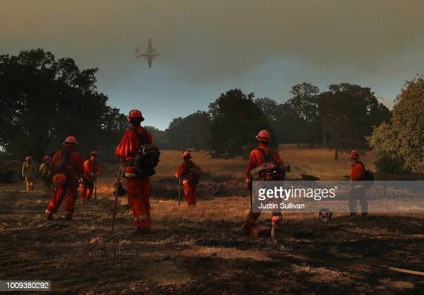 Inmate firefighters look on as a firefighting aircraft prepares to drop fire retardant ahead of the River Fire as it burns through a canyon on August...