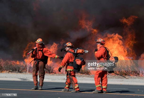 Inmate firefighters prepare to put out flame on the road leading to the Reagan Presidential Library during the Easy Fire in Simi Valley California on...