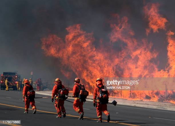 Inmate firefighters prepare to put out flames on the road leading to the Reagan Library during the Easy Fire in Simi Valley California on October 30...