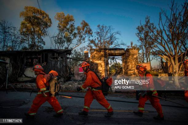 TOPSHOT Inmate firefighters walk past a burnt home on Tigertail road during the Getty Fire in Brentwood California on October 28 2019 More than 1000...