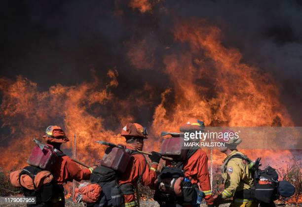 Inmate firefighters walk the road leading to the Reagan Library during the Easy Fire in Simi Valley California on October 30 2019 Firefighters in...