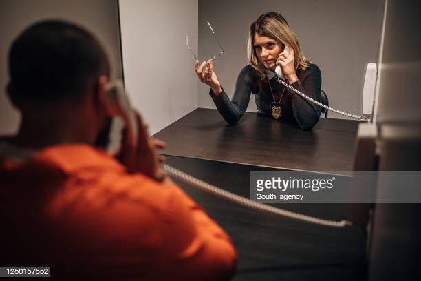 刑務所の訪問室で女性刑事と話している受刑者 - 執行猶予 ストックフォトと画像