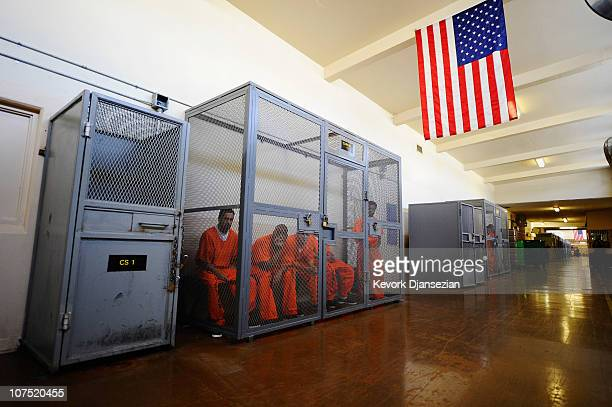Inmates at Chino State Prison sit inside a metal cage in the hallway on December 10 2010 in Chino California Inmates wait in the cages to be assigned...