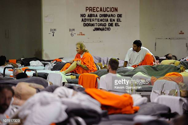 Inmates at Chino State Prison which houses 5500 inmates crowd around double and triple bunk beds in a gymnasium that was modified to house 213...