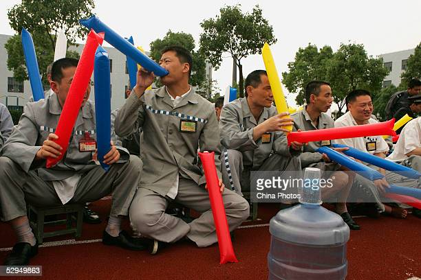 Inmates cheer during a football match in which Chinese football star Fan Zhiyi participates with inmates at Qingpu Prison on May 18 2005 in Shanghai...