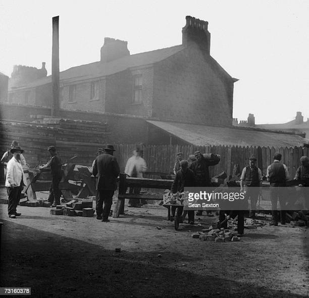 Inmates chopping wood and breaking stones at a British workhouse circa 1880