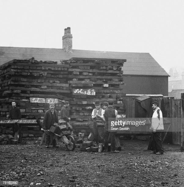 Inmates chopping wood at a British workhouse, circa 1880.
