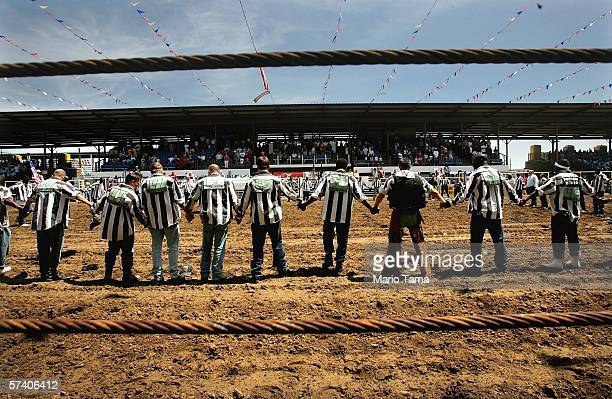 Inmates hold hands for a prayer at the beginning of the Angola Prison Rodeo at the Louisiana State Penitentiary April 23 2006 in Angola Louisiana The...
