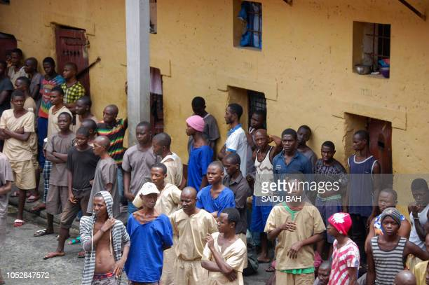 Inmates of the Kenema Prison stand in the prison's courtyard in Kenema on October 12 2018 In 2016 Sierra Leone's Human Rights Commission lashed the...