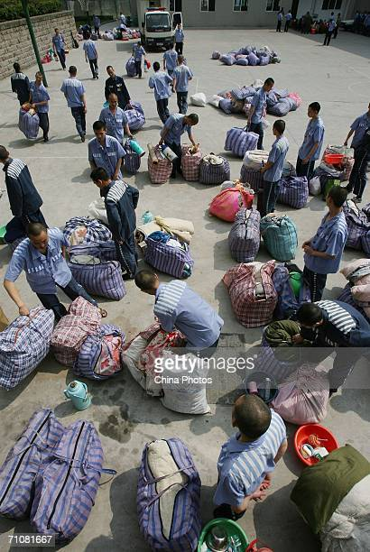 Inmates pick up their belongings as they arrive at Yuzhou Prison during a prisoner transfer operation on May 30 2006 in Chongqing Municipality China...